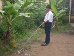 Em Hồ Lâm Hữu Luân sử dụng cây kẹp nhặt rác làm vệ sinh xung quanh trường