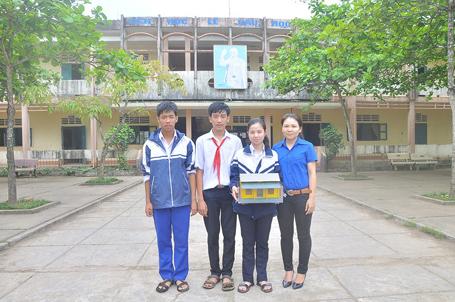 """Nhóm 3 tác giả Thanh Thiên, Duy Khánh, Tố Như cùng cô giáo Nguyễn Thị Vân bên mô hình """"ngôi nhà sống chung với lũ""""."""