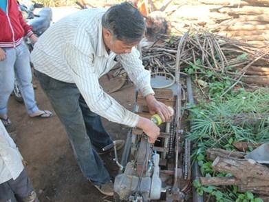 Ông Phan Ngọc Tấn bên chiếc máy cày gắn động cơ xe máy đang trong quá trình hoàn thiện.