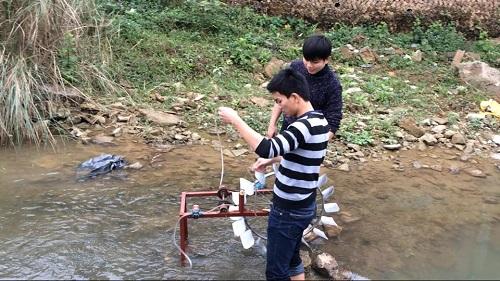 """Hai """"nhà phát minh"""" đang thử chạy thiết bị đưa nước lên cao không cần dùng điện tại một con suối"""