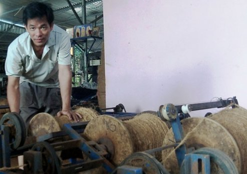 Anh Thuận và máy xe chỉ xơ dừa chạy bằng điện cho năng suất cao do anh sáng chế - Ảnh: Sơn Bình