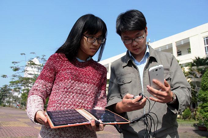 Hai bạn Đoàn Trần Viên và Nguyễn Thủy Tiên thử nghiệm sản phẩm sạc pin điện thoại bằng năng lượng mặt trời - Ảnh: Phan Thành