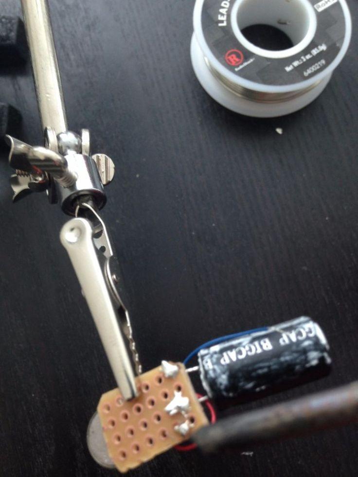 Lắp động cơ rung vào bảng mạch in. Một chân được hàn vào 1 chân cắm đực ( header pin ), một chân được hàn vào chân đầu ra của tụ. Ảnh: http://www.instructables.com