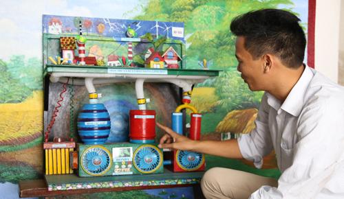 Thầy giáo Phạm Sơn Thu bên mô hình máy thu và xử lý bão trong lòng đất. Ảnh: Phương Vy.