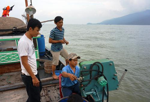 Phan Thành Nhân (áo trắng) và Lê Văn Hoàng (áo sọc xanh) kiểm tra hiệu quả sử dụng của máy thu câu khi đang hoạt động trên biển - Ảnh: An Dy