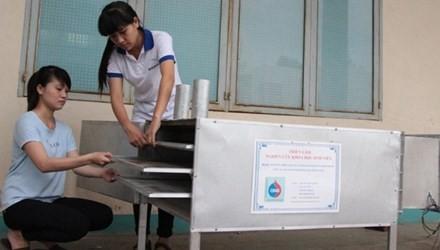 Các bạn sinh viên bên sản phẩm ứng dụng từ nhiệt thải lò bánh tráng để sấy khô bánh.